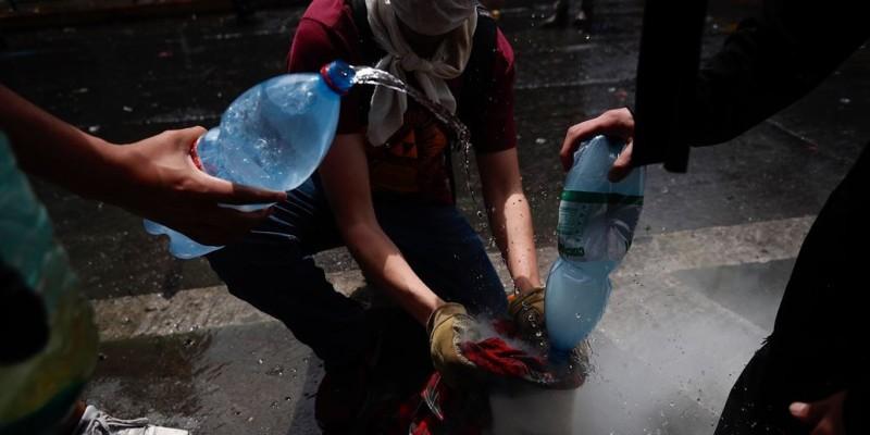 外媒拍到智利示威者對催淚彈灑水,使其失去效用。(歐新社)