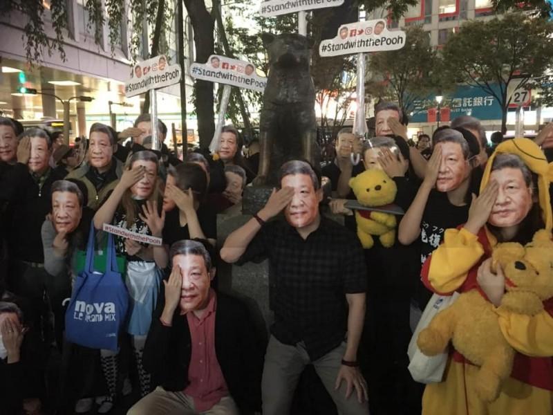 百名在日香港人聚在日本澀谷街頭,戴著習近平面具「慶萬聖」。(圖擷取自umbrella.movement.exhibition@FB)