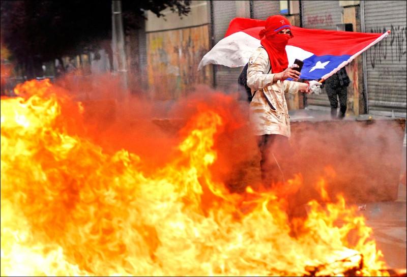 在智利中部的康塞普松市(Concepcion),示威者拿該國國旗,焚毀當局設下的路障。(路透)