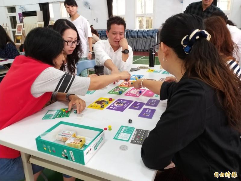 志工家長參與反毒情境桌遊,以「虛擬人生」的遊戲規則模擬各種可能觸及毒品的情境,明瞭一旦碰觸毒品,再染毒的機率將大為提高。(記者廖雪茹攝)