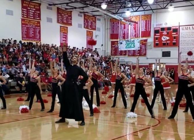 美國一名牧師在高中啦啦隊表演時亂入,沒想到竟跟著學生一起熱舞。(圖擷自Cardinal Gibbons High School FTL臉書)