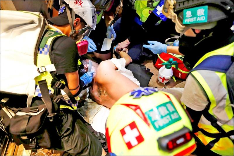 香港防暴警察2日晚間在銅鑼灣地區發射催淚彈驅散「反送中」示威者,其中一枚疑似中國製造的催淚彈竟大量噴火,意外被擊中的急救志工背部大面積燒傷,其他同袍見狀緊急上前為他處理傷勢。(路透)