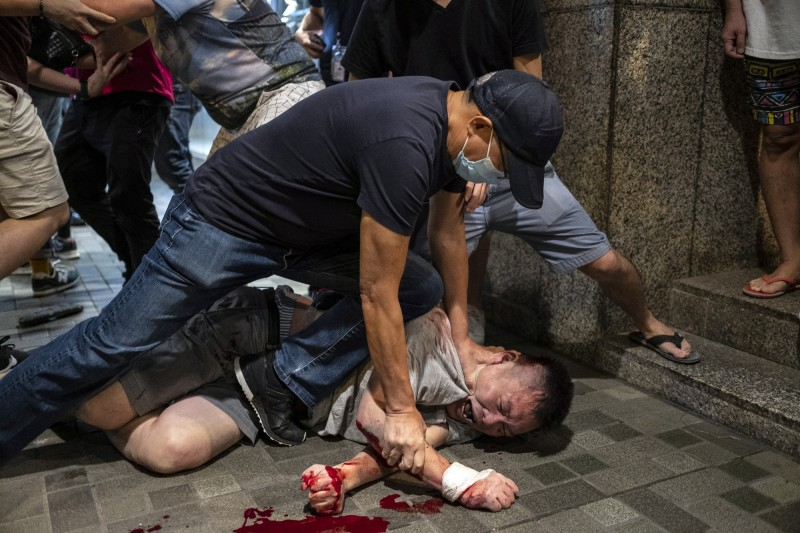 香港反送中抗爭,1男持刀傷人被民眾壓制。(彭博)