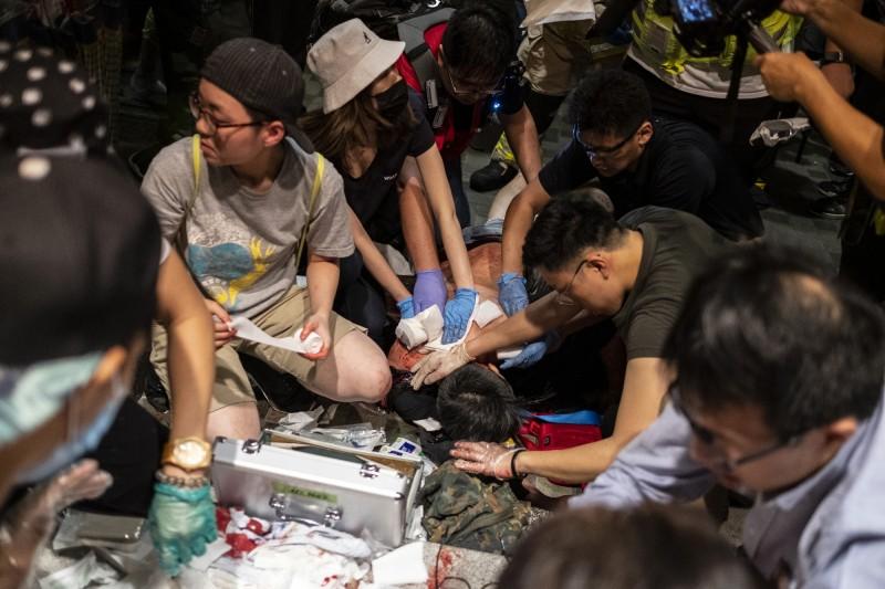 香港太古商場路人被凶嫌持刀殺傷,現場民眾急救人。(彭博)