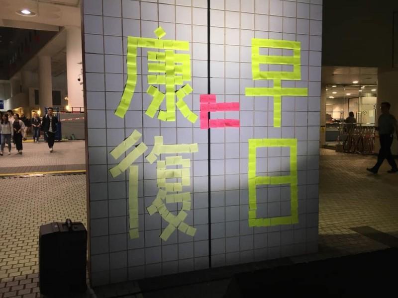 科大同學以便條紙在牆上貼成「早日康復」的字樣。(圖擷取自臉書_香港科技大學學生會編輯委員會 The Editorial Board, HKUST Students' Union)