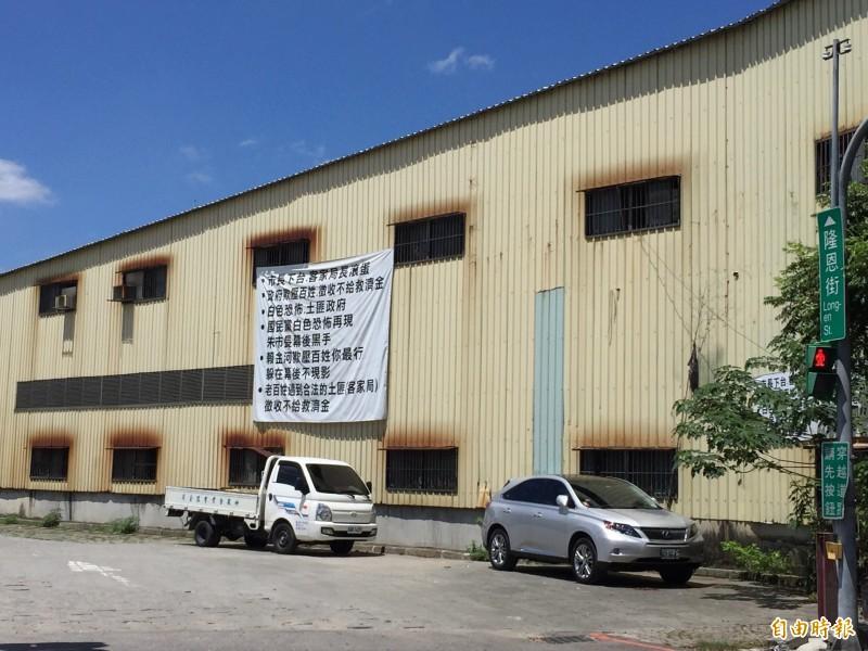 在客家文化園區對面的鐵皮工廠貼上布條表達不滿。(記者邱書昱攝)