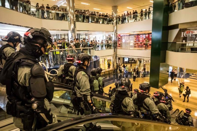 香港《立場新聞》特約攝影記者Joey Kwok表示,被捕期間,港警一度無理要求要前往Joey家中搜屋,遭其律師拒絕。圖為鎮暴警察衝入太古商場。(法新社)