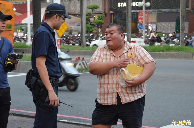 「髮蠟哥」下午抱著一袋冥紙跑到屏東縣警局大門口,揚言點火自焚,被警方制止。(記者李立法攝)