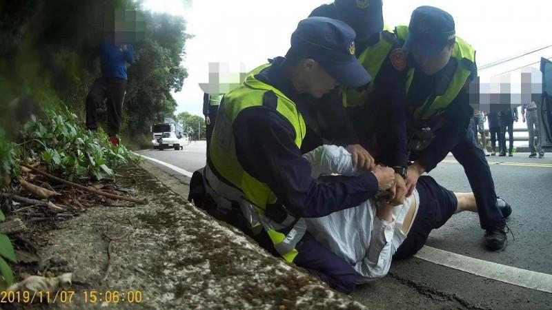 警方將朱男從自小客內拖拉出,隨即壓制在地上銬。(記者陳賢義翻攝)