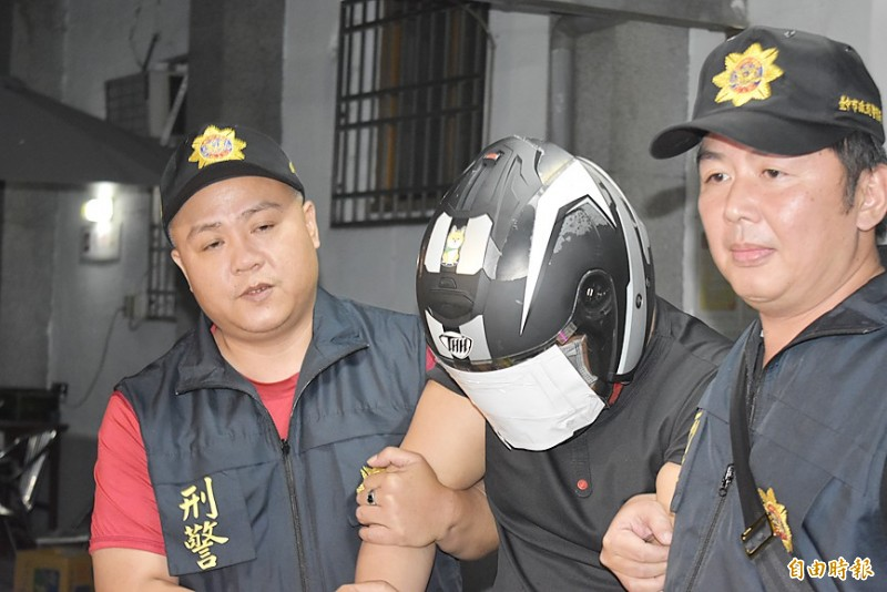 The suspect in a murder case, surnamed Chen, center, is yesterday escorted to the Taichung District Prosecutors' Office by Criminal Investigation Bureau officers. Photo: Chang Jui-chen, Taipei Times