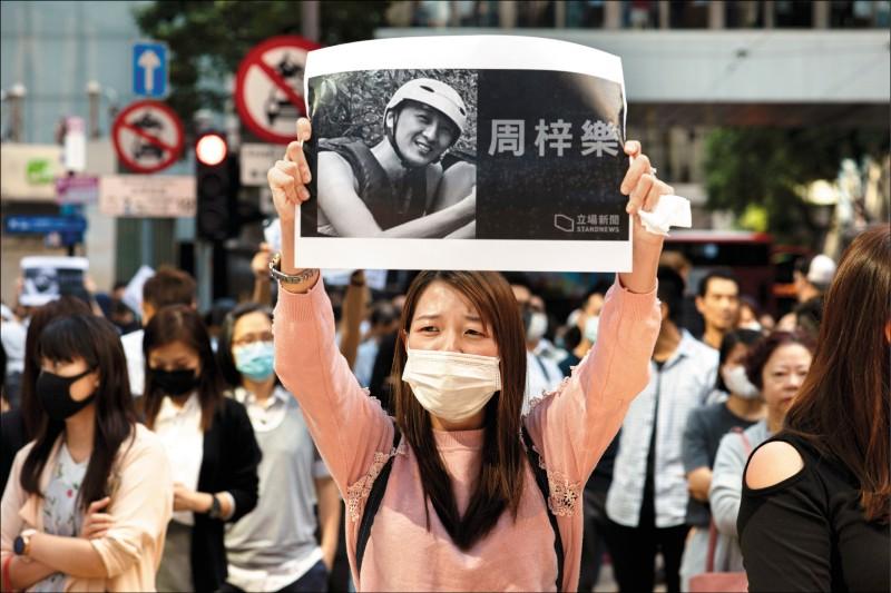 一名年輕女子舉著從香港網路媒體「立場新聞」網頁所印的周梓樂照片。(歐新社)