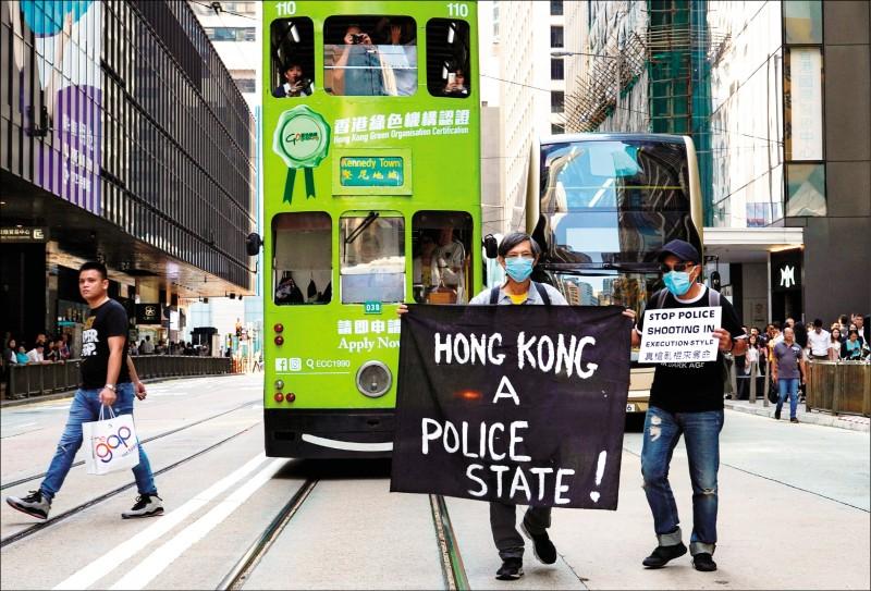 示威者舉起「香港是警察國家」、「你們是殺人犯」的標語,對警方濫暴表達不滿。(美聯社)