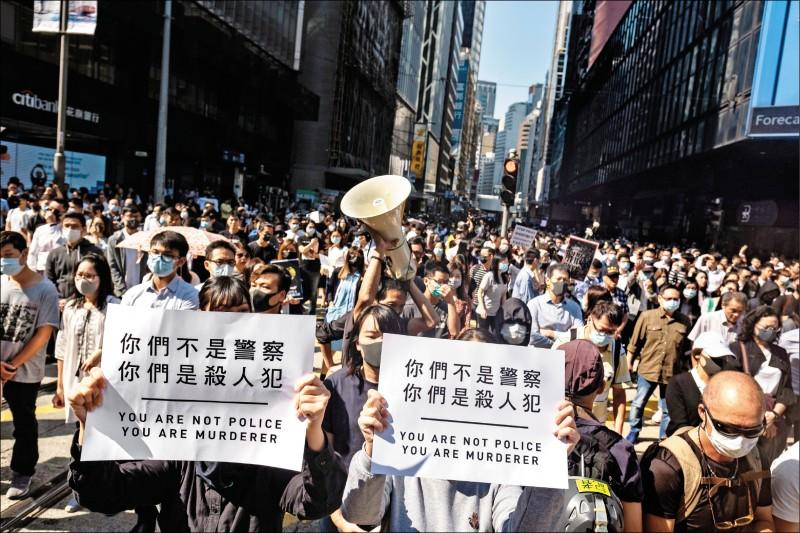 示威者舉起「你們是殺人犯」的標語,對警方濫暴表達不滿。(彭博、美聯社)