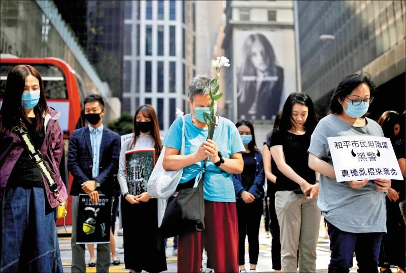 香港市民八日拿鮮花,自發性地聚集悼念周梓樂的早逝。(路透)