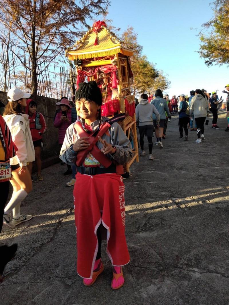 參加半馬組的女選手全程揹著坐在神轎中的媽祖神像跑步。(南投縣府提供)