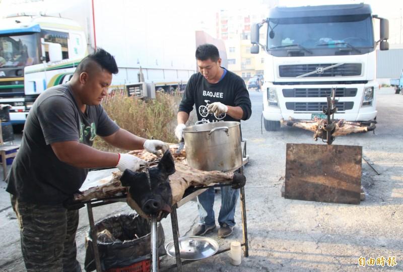田中馬賽道補給豐富,民眾忙得烤大豬供應。(記者陳冠備攝)