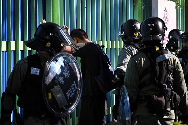 鎮暴警察早早就進駐香港各區,攔查路上的市民。(法新社)