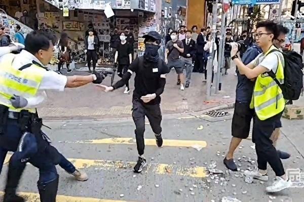港警至少以3發實彈射向民眾,其中一名手無寸鐵的黑衣人腹部中槍倒地。(影片擷圖)