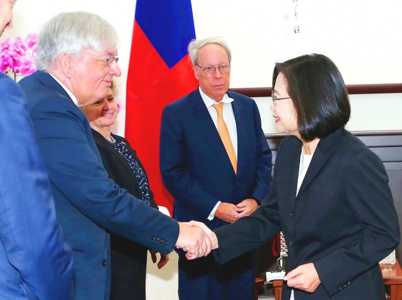 President Tsai Ing-wen, right, shakes hands with former American Institute in Taiwan chairman Raymond Burghardt at the Presidential Office in Taipei yesterday. Photo: CNA