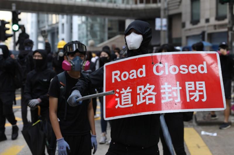 黑衣示威者舉著道路封閉的交通標誌。(歐新社)