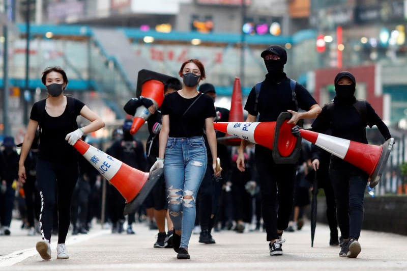 示威者拿著交通錐,準備前往下個地點設置路障。(路透)
