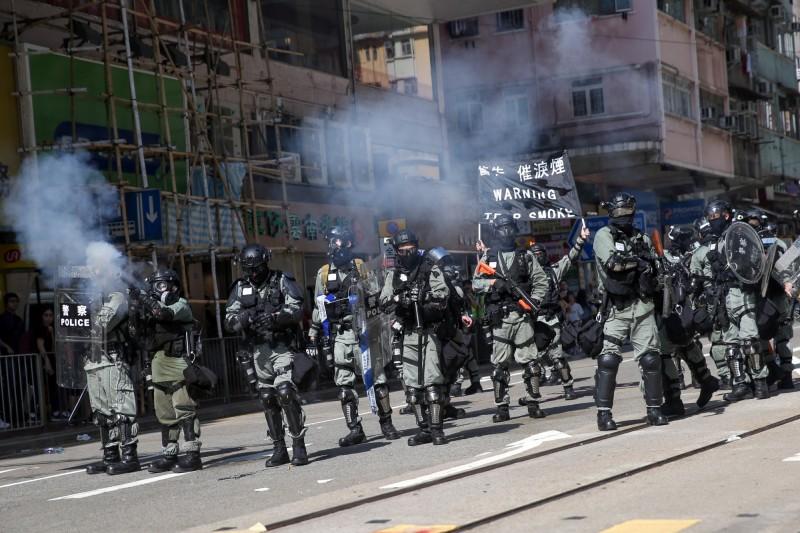 在西灣河,鎮暴警察高舉黑旗警告會發射催淚彈。(歐新社)