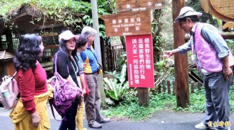 南投縣溪頭自然教育園區志工向遊客宣導不要餵食獼猴等野生動物。(記者謝介裕攝)