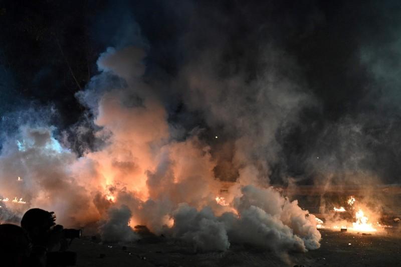 香港警方強攻中文大學,晚間持續發射大量催淚彈,學生則生起火堆頑抗,夜色中火光夾雜煙霧,雙方互不退讓;晚間10點左右,水砲車到達二號橋,並一度發射藍色水。(法新社)