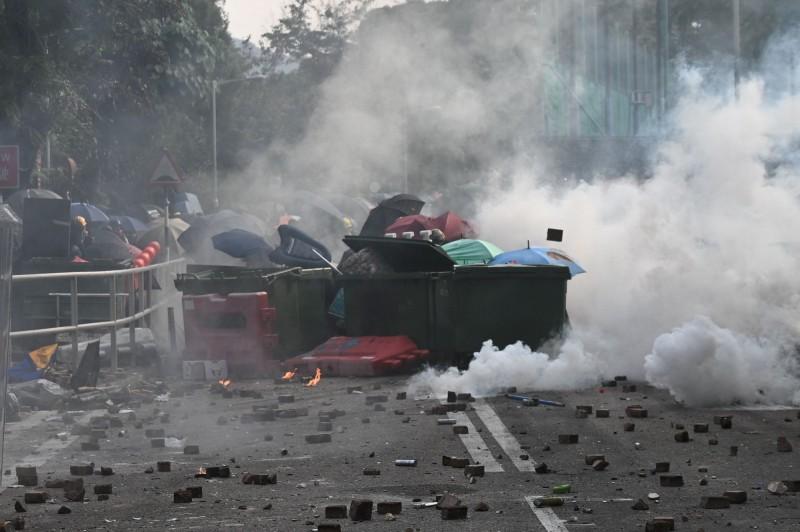 示威者以雜物堆積成掩護,並撐傘作為防護。(美聯社)
