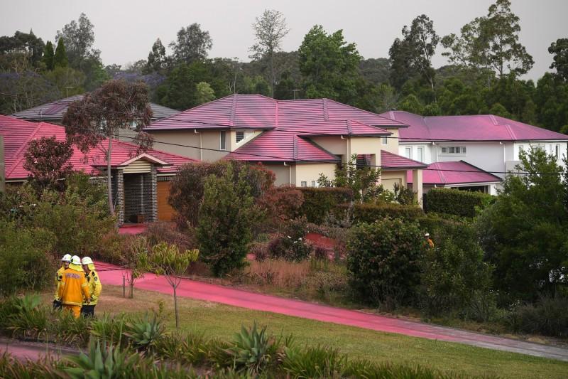 當局為保護房屋,利用消防直升機噴灑阻燃劑,汽車、房屋和道路被一層粉紅色阻燃劑覆蓋。(歐新社)
