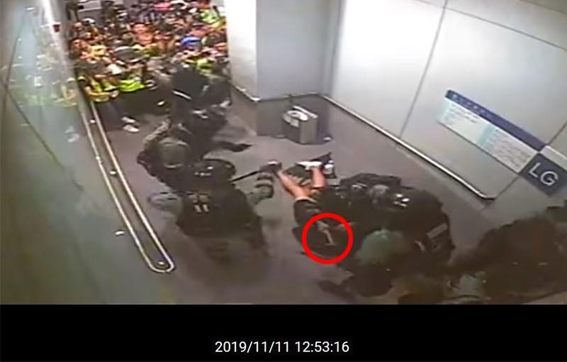 穿著黑色膝上褲的青年趴在地上,防暴警察把疑似槌子的物品放入青年的包裡。(擷取自Youtube)
