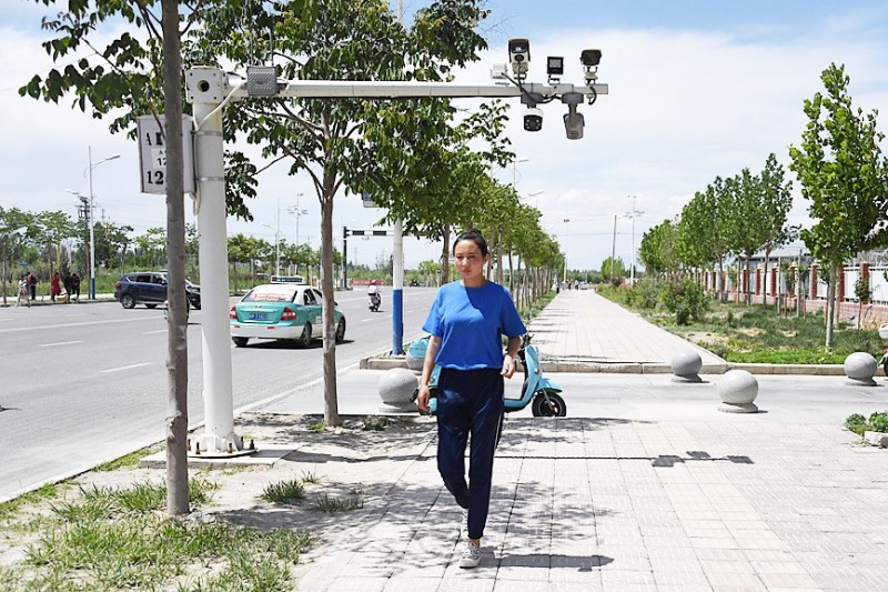 A woman walks below surveillance cameras in Xinjiang region's Akto, China, on June 4. Photo: AFP