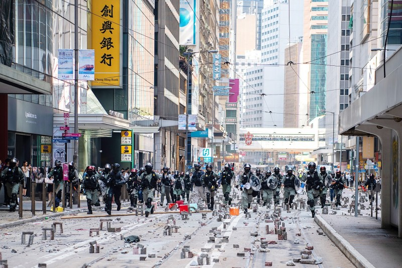 Riot police run down a road covered with bricks in the Central business district of Hong Kong yesterday. Photo: Bloomberg