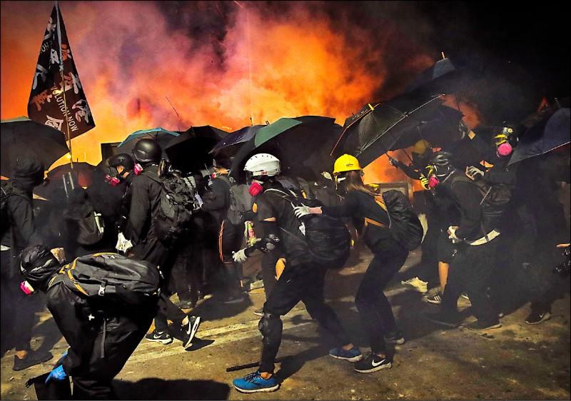 香港中文大學學生十二日與警方激烈對抗到深夜,以雨傘抵擋警方的催淚彈攻勢。(美聯社)