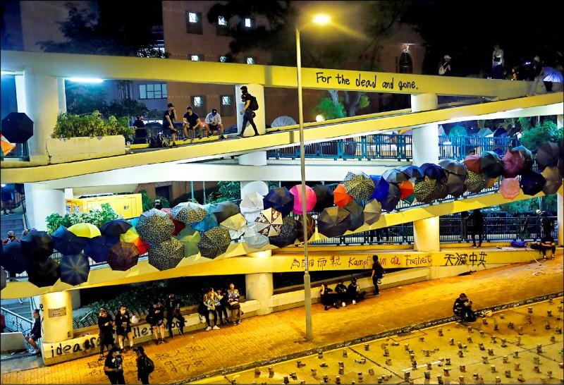十二日整天至十三日凌晨,香港警方對香港中文大學發動攻擊,發射逾千枚催淚彈,但學生堅守校園,打死不退。圖為十三日的中大校園一隅,學生將用來抵擋催淚彈的雨傘掛在行人天橋的扶手上。 (路透)