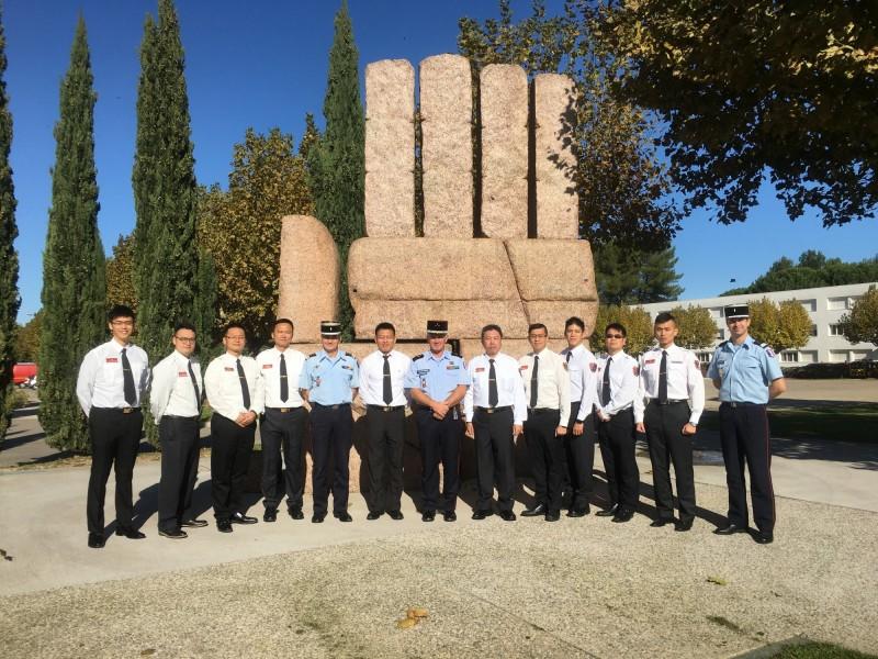 新北市消防局代表台灣首度遠赴法國消防官高等學院,訓練前與法方人員在學院精神象徵—救助之手前方合影。(記者吳仁捷翻攝)