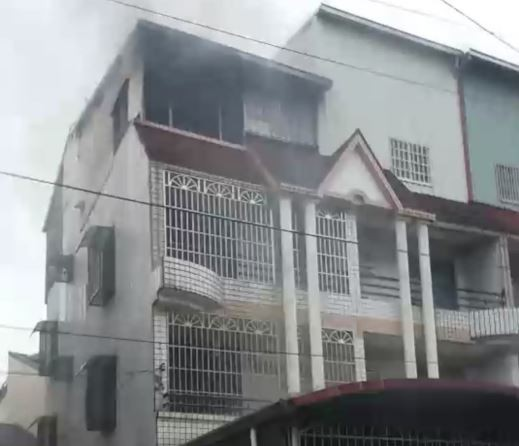 民宅頂樓鐵皮加蓋,起火燃燒,警消人員佈水線搶救。(現場民眾提供)