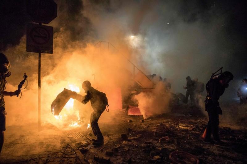香港中文大學12日爆發警民衝突,示威者設置燃燒路障堵塞交通。(法新社)