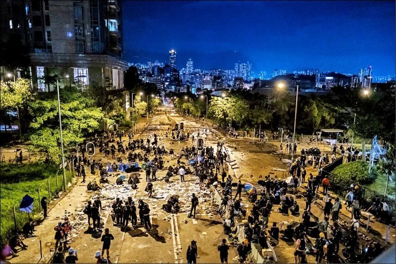 示威學生十二日晚間聚集在城大學生宿舍外。(彭博)