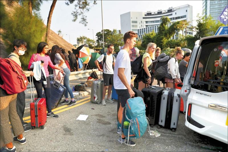 香港中文大學的國際學生,15日搭車撤離校園。(路透)