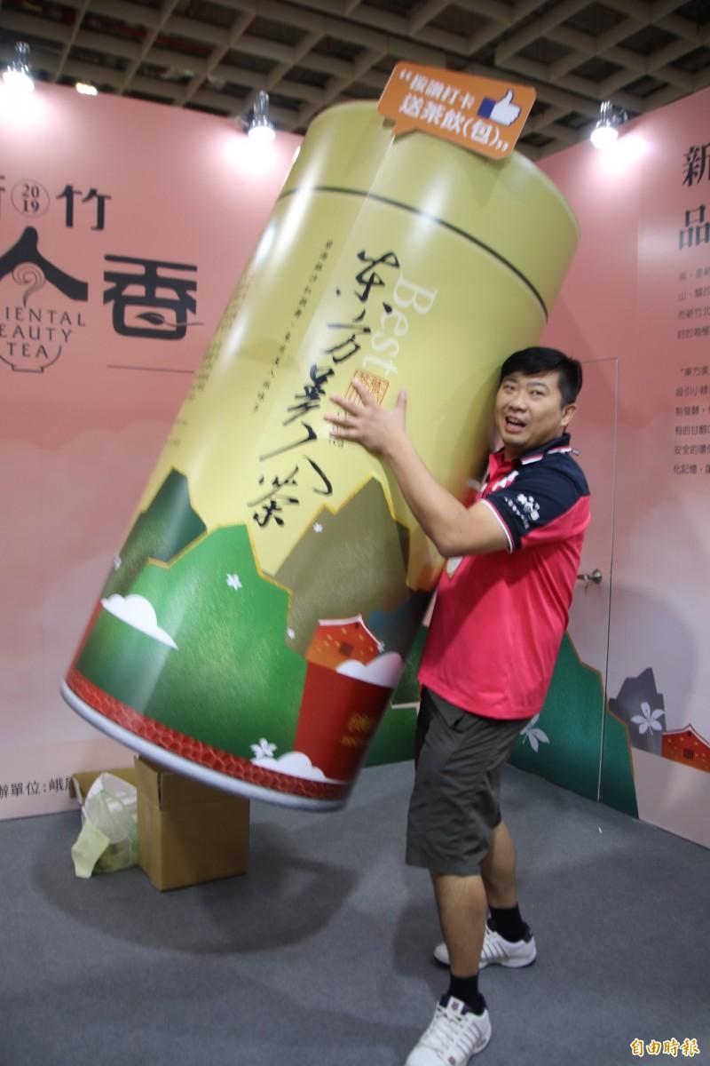 想抱得「美人歸」很簡單!新竹縣的「新竹美人香」展區,歡迎來客跟大茶罐玩創意拍且分享、或現場打卡按讚,就可抱回東方美人的罐裝茶飲或茶包。(記者黃美珠攝)
