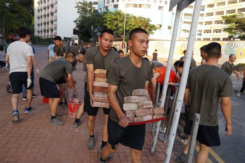 下午4時,九龍塘駐港解放軍軍營外突然出現數十名軍人,協助在附近的道路上清除路障。(法新社)