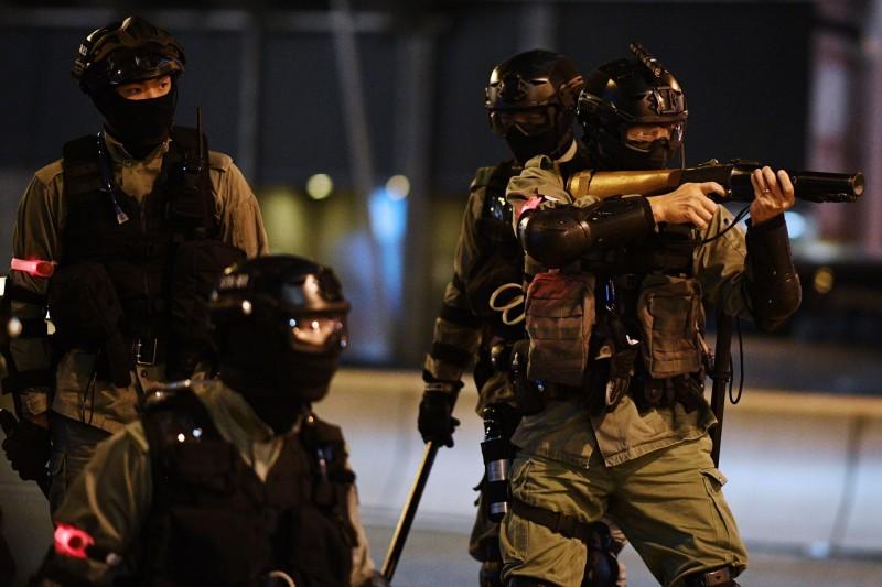 晚間約凌晨1時,有港警推撞一名記者,並朝他背後開槍。(法新社)