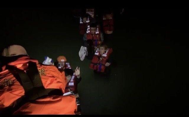 金門岸巡隊協助受困的男大生穿上救生衣,一一接駁上小艇。(圖由金門岸巡隊提供)