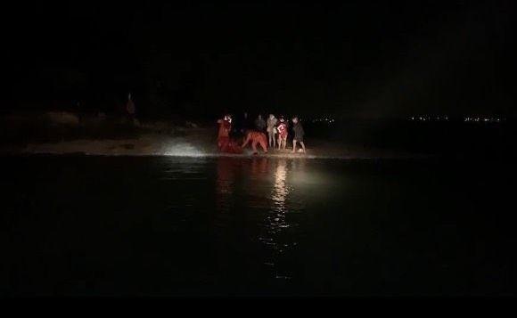 金門岸巡隊派員登上建功嶼,協助男大生穿上救生衣脫困。(圖由金門岸巡隊提供)