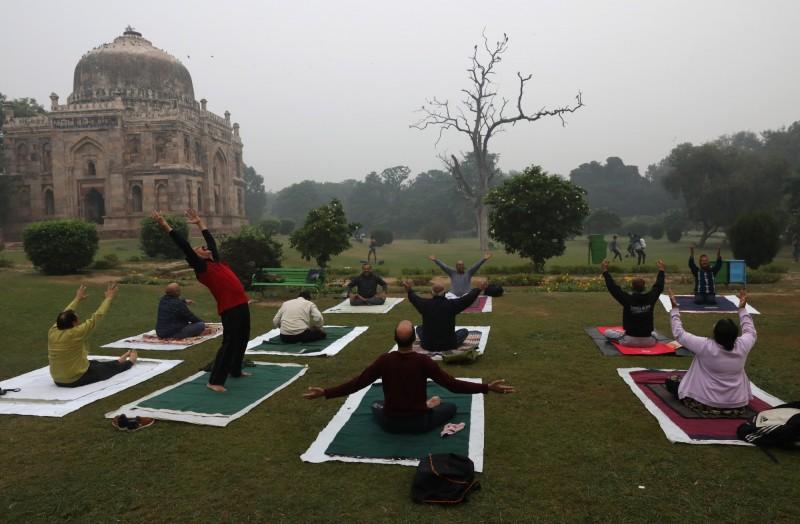 儘管空汙嚴重,仍有許多印度民眾一早就出門做瑜珈。(歐新社)