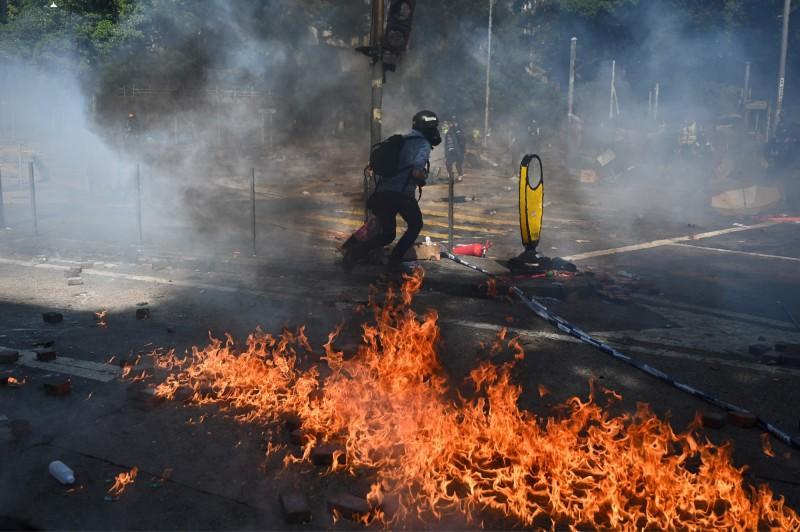 示威者投擲汽油彈還擊,現場火光瀰漫。(法新社)