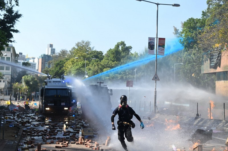 警方以水炮車射出藍色水柱及催淚水劑,試圖驅離示威者。(法新社)