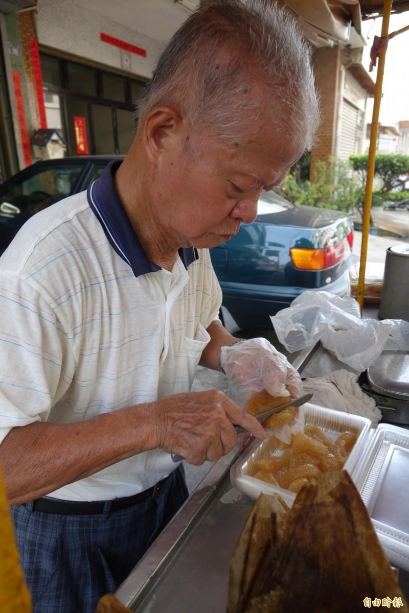 鹿港龍山寺「肉包阿伯」,夏天賣涼粽,總是專注把涼粽切成小塊裝盒賣。(檔案照,記者劉曉欣攝)