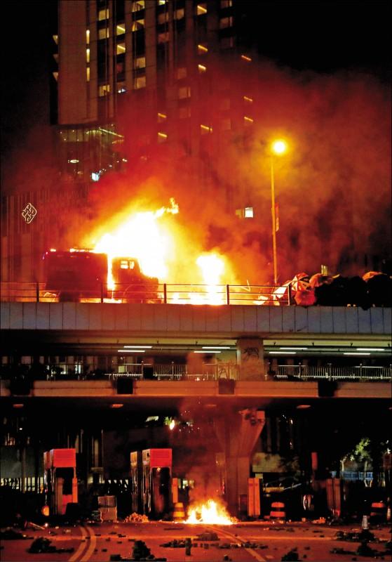 大批「反送中」抗爭者17日在鄰近香港理工大學的紅磡海底隧道出入口,與警方爆發激烈衝突,警方出動的「銳武」裝甲車車身起火。(路透)